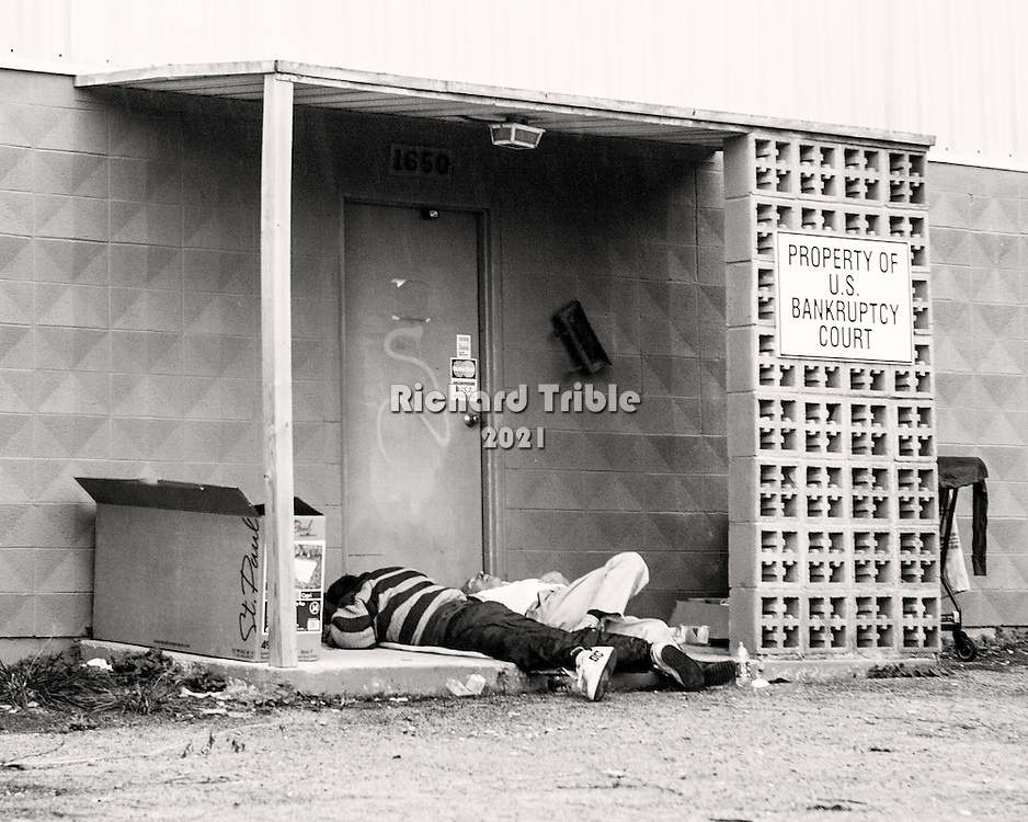 """Two guys sleeping. Sign says, """"Property of U.S. Bankruptcy Court""""."""