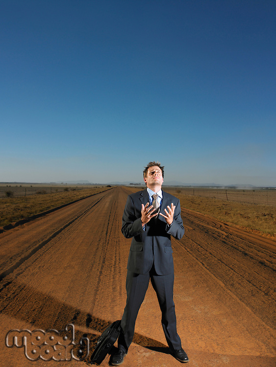 Frustrated busiessman in middle of deserted road
