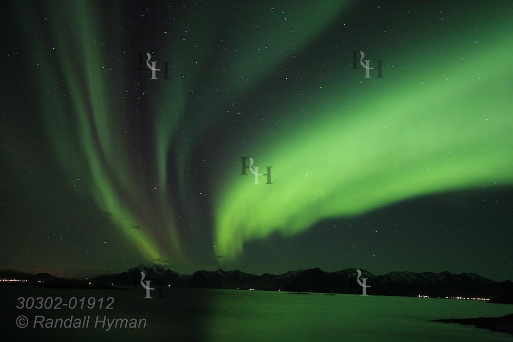 Northern Lights, Aurora Borealis, shimmer and glow over mountains around Henningsvaer; Lofoten Islands, Norway.