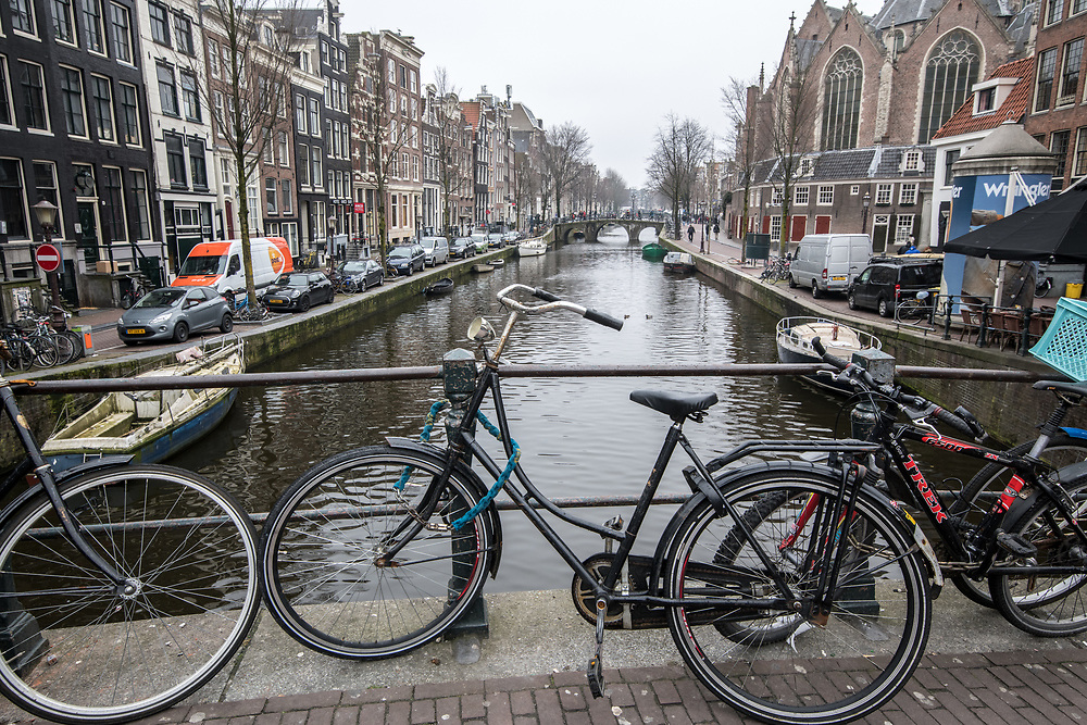 A bike is chained a to a bridge overlooking a canal  in Amsterdam Netherlands.