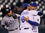 Tampa Bay Rays James Loney, left, runs past as Kansas City Royals Mike Moustakas, center, and Eric Hosmer, right, celebrate their 9-8 win over the Rays in a baseball game at Kauffman Stadium in Kansas City, Mo., Wednesday, May 1, 2013.  (AP Photo/Colin E. Braley).