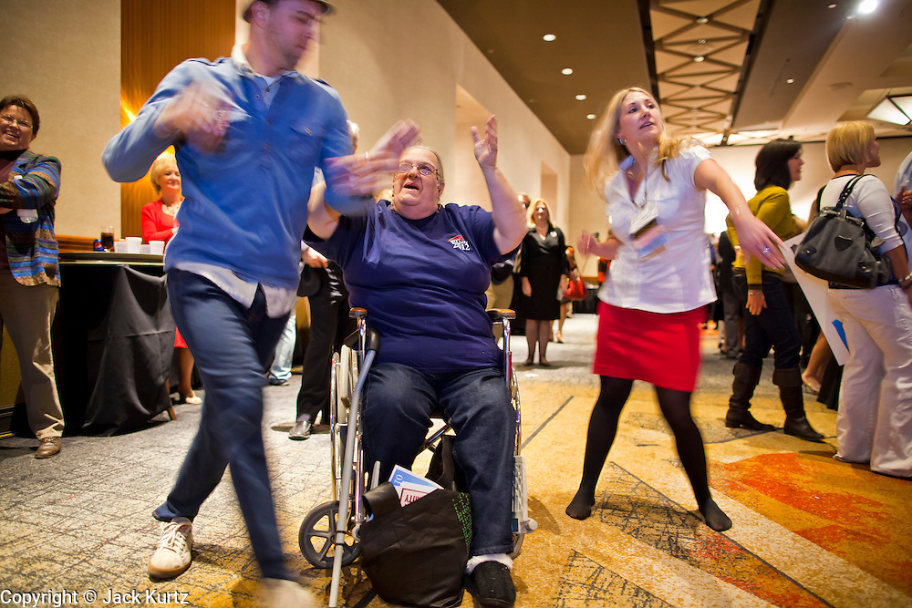 28 FEBRUARY 2012 - PHOENIX, AZ:   Mitt Romney supporters dance when primary election results from the Arizona show Romney winning the state are flashed on a TV screen. Several hundred Romney supporters crowded into a ballroom in a Phoenix hotel to watch primary results from Michigan and Arizona. Romney won the night, scoring a tight win in the Michigan Republican Presidential primary and a comfortable win in the Arizona Republican Presidential primary.       PHOTO BY JACK KURTZ