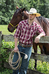 good looking cowboy leaning on a fence near a horse