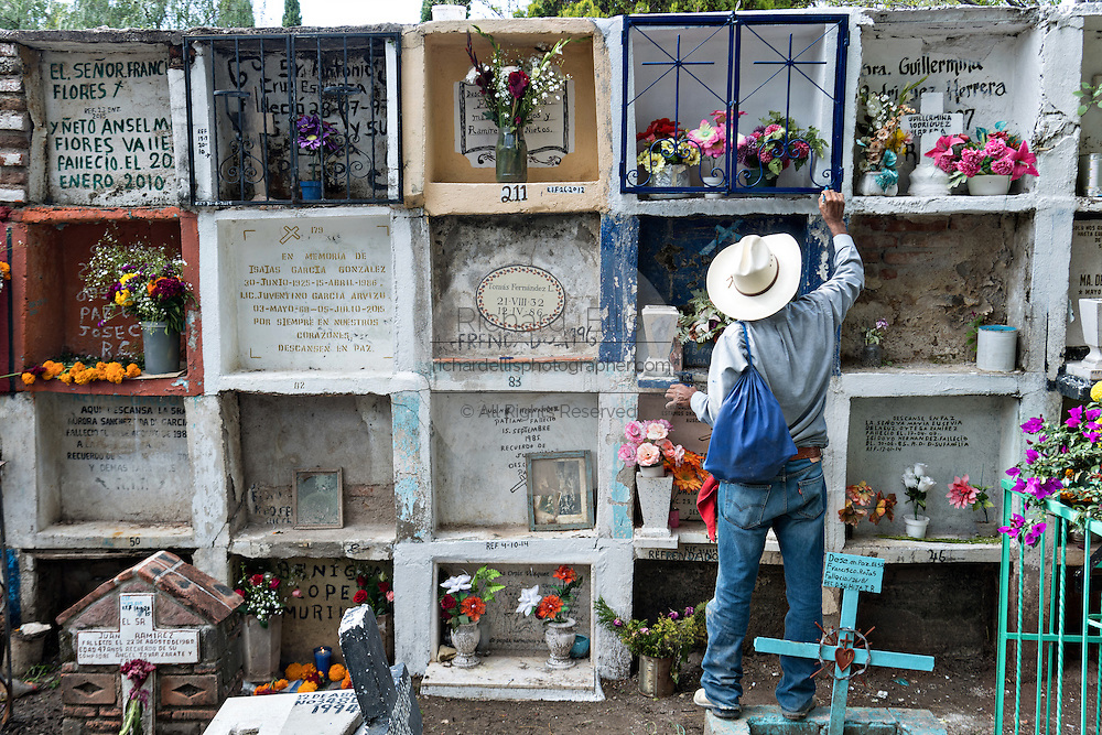 A Mexican man paints the grave of a relative in the Nuestra Señora de Guadalupe cemetery during the Day of the Dead festival November 1, 2016 in San Miguel de Allende, Guanajuato, Mexico. The week-long celebration is a time when Mexicans welcome the dead back to earth for a visit and celebrate life.
