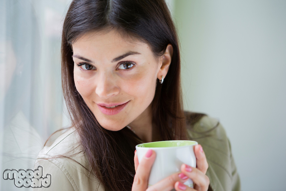 Portrait of confident young businesswoman with coffee cup in office