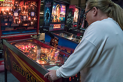 © Licensed to London News Pictures. 12/08/2018. LONDON, UK. A woman plays a pinball machine at Play Expo London, a video games show featuring consoles, handhelds, computers, vintage arcades and pinball machines, organised by Replay Events taking place at the Printworks in Canada Water, East London.  Photo credit: Stephen Chung/LNP