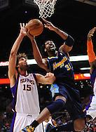 Mar. 10, 2011; Phoenix, AZ, USA; Denver Nuggets center Nene (31) puts up a basket against the Phoenix Suns center Robin Lopez (15) at the US Airways Center. The Nuggets defeated the Suns 116-97.  Mandatory Credit: Jennifer Stewart-US PRESSWIRE