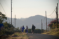 A woman and her children walking to school at sunrise along a road in Mbabane, Swaziland. The Kingdom of Swaziland (population 1.1m), a small, landlocked country in southern Africa was bordered by South Africa on three sides and Mozambique to the east, with Mbabane as its administrative capital. At the start of the 21st century, the country had the highest incidence per head of population of HIV/Aids in the world and and high levels of poverty mainly in rural areas where 75 per cent of the population lived.