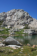 Sunlit cliff overlooks small lake in Sixty Lakes Basin, King's Canyon National Park