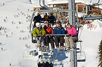 A group rides the Glacier chairlift at Blackcomb Mountain, Whistler, BC on a sunny winter day.