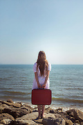 a girl with a red suitcase standing at the sea
