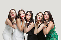 Five young women blowing kisses over gray background