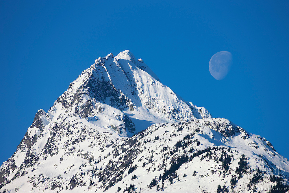 The moon sets behind Alpha Mountain, a 2305-meter (7562-feet) peak in Tantalus Provincial Park, British Columbia, Canada. The mountain is located near the town of Brackendale.