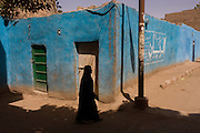 A local woman walks past a blue painted wall in a village near Medinet Habu on the West Bank of Luxor, Nile Valley, Egypt.