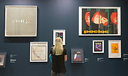 """© Licensed to London News Pictures. 21/10/2013. London, England. A visitor stands in front of pop art posters. The Exhibition """"Pop Art Design"""" opens at the Barbican Art Gallery/Barbican Centre running from 22 October 2013 to 9 February 2014. The exhibition brings together 200 works by 70 artists and designers including Peter Blake, Andy Warhol and Roy Lichtenstein. Photo credit: Bettina Strenske/LNP"""
