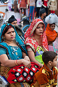 Indian women travel by rickshaw in crowded street scene in city of Varanasi, Benares, Northern India