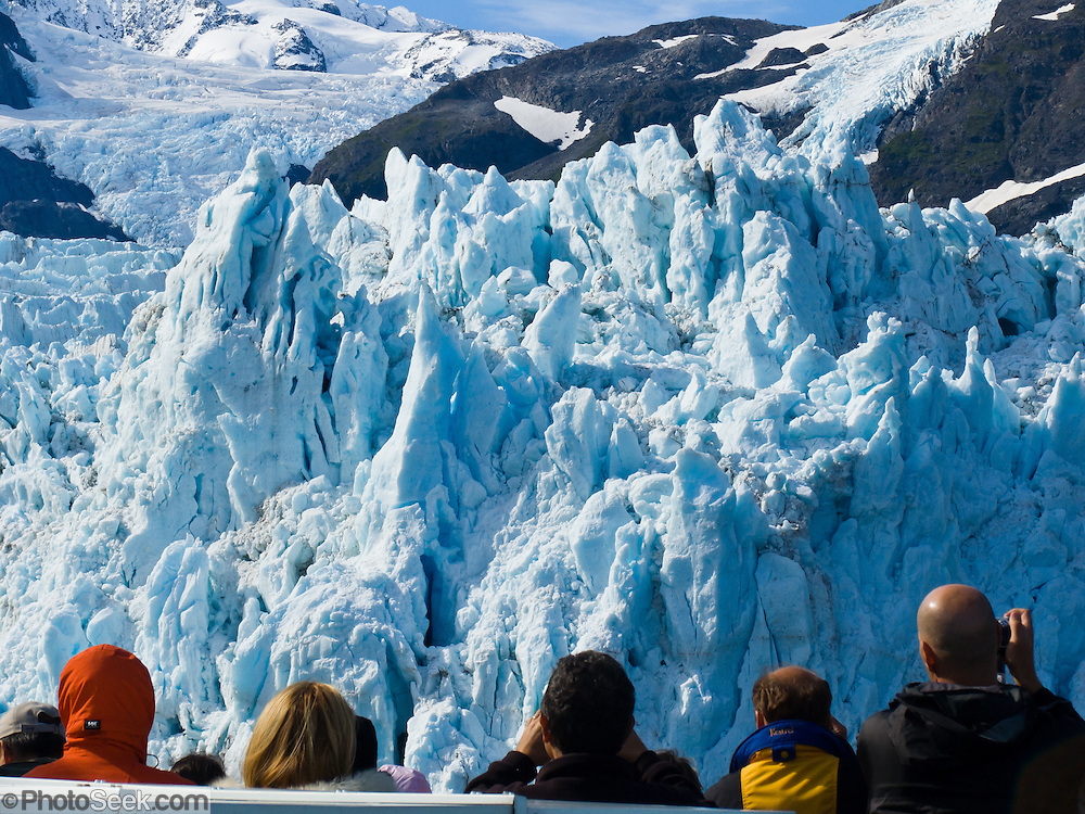 The tidewater Surprise Glacier pours from the steep and glaciated Chugach Mountains into Harriman Fjord in Prince William Sound, Alaska, USA. Prince William Sound is surrounded by Chugach National Forest (the second largest national forest in the USA). Tour spectacular Prince William Sound by commercial boat from Whittier, which sits strategically on Kenai Peninsula at the head of Passage Canal. Whittier is a port for the Alaska Marine Highway System, a ferry service which operates along the south-central coast, eastern Aleutian Islands, and the Inside Passage of Alaska and British Columbia, Canada. Cruise ships stop at the port of Whittier for passenger connections to Anchorage (by road 60 miles) and to the interior of Alaska via highway and rail (the Denali Express). Known by locals as the Whittier tunnel or the Portage tunnel, the Anton Anderson Memorial Tunnel links Whittier via Portage Glacier Highway to the Seward Highway and Anchorage. At 13,300 feet long (4050 m), it is the longest combined rail and highway tunnel in North America. Whittier was severely damaged by tsunamis triggered by the 1964 Good Friday Earthquake, when thirteen people died from waves reaching 43 feet high (13 meters).