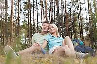 Full length of romantic young hiking couple relaxing in forest