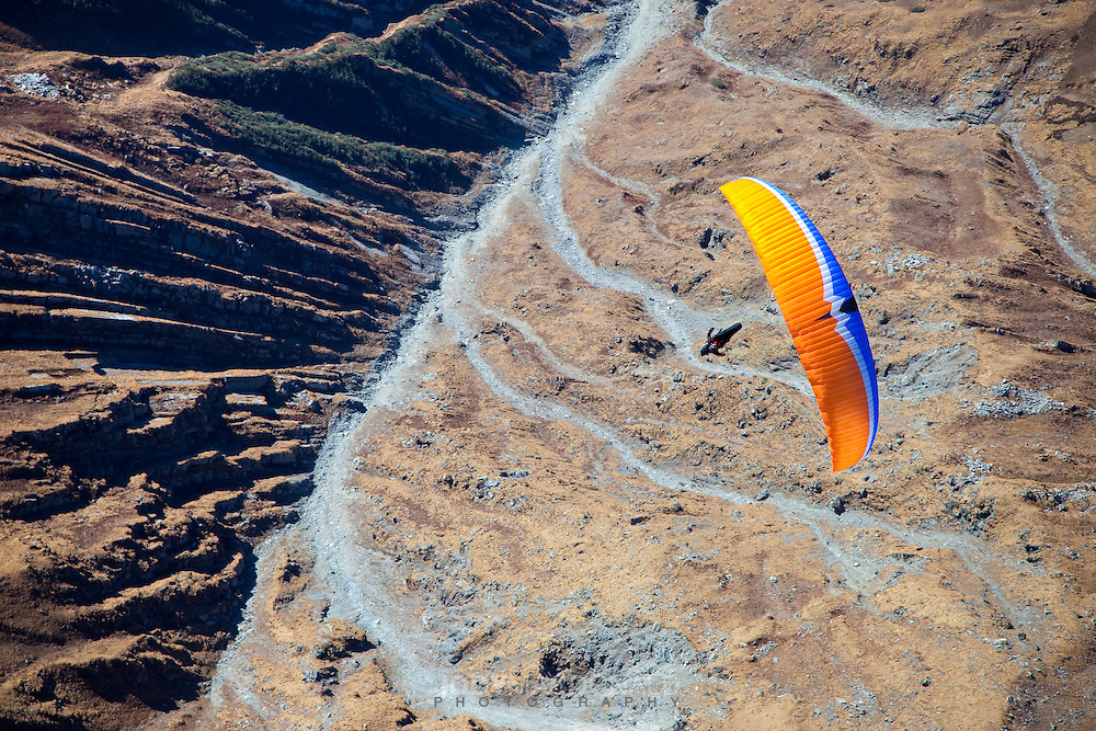 Paraglider soars over the high himalayan mountains above the town of Bir, India in Himachal Pradesh