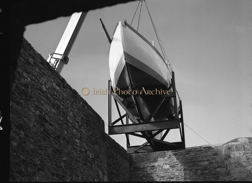 "The ""Asgard "" at Kilmainham Jail..1979..01.04.1979..04.01.1979..1st April 1979..The historic yacht ""Asgard"" owned by Erskine Childers was brought to Kilmainham Jail,Dublin. The vessel had to be hoisted ,by crane,over the outer wall of the jail. It was placed as part of a future exhibition to be set up by The National Museum..Image shows the ""Asgard"" being lowered into position inside the jail's wall."