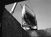 """The """"Asgard """" at Kilmainham Jail..1979..01.04.1979..04.01.1979..1st April 1979..The historic yacht """"Asgard"""" owned by Erskine Childers was brought to Kilmainham Jail,Dublin. The vessel had to be hoisted ,by crane,over the outer wall of the jail. It was placed as part of a future exhibition to be set up by The National Museum..Image shows the """"Asgard"""" being lowered into position inside the jail's wall."""