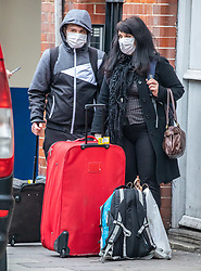 © Licensed to London News Pictures. 19/03/2020. London, UK. A couple in protective masks with suitcases next to London Victoria bus Station as London prepares to shutdown over the Coronavirus pandemic crisis. Photo credit: Alex Lentati/LNP