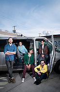 Milagres pose with their tour van by the Doug Fir Lounge in Portland.
