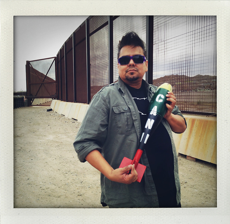 Artist Angel Cabrales with a 'flan pudding tipped' bomb at the border fence in El Paso, Texas. <br /> <br /> LaFronteraArtistsAlongTheUsMexicanBorder<br /> http://borderartists.com