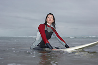 Female surfer sitting on surfboard in water low angle view
