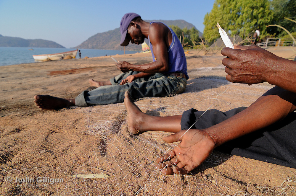 Richard Lucas (close) and Richard Pofera (far) repair their fishing net on the shore of Cape Maclear, Lake Malawi, Malawi.