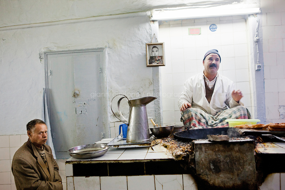 Kairouan, Tunisia - 18 December, 2011: A man cooks breakfast at dawn in Kairouan, Tunisia on 18 December, 2011. Said Ferjani, 54, senior member of the political and communication bureau of the Nahda (Renaissance) party, started his activism in the Negra mosque of his hometown Kairouan when he was 16 years old, debating on politics, philosophy, economy and world events. In 1989 former dictator Zine El Abidine Ben Ali turned against Nahda (or Ennahda) and jailed 25,000 activists. Said Ferjani was jailed and tortured. He then flew Tunisia and moved to the UK. He came back to Tunisia after 22 years, after former dictator Ben Ali flew the country.<br /> <br /> Gianni Cipriano for The New York Times