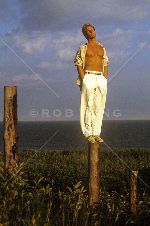 man with an open shirt standing on a wooden pole near the ocean in Montauk, NY