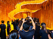 22 OCTOBER 2017 - BANGKOK, THAILAND: People in black mourning clothes walk under and photograph the number 9 written in Thai script in a marigold floral display in front of Pak Khlong Talat, the flower market, in Bangkok. The number 9 in Thai script is the design to honor Rama IX, Bhumibol Adulyadej, the Late King of Thailand, and the 9th king in the Chakri Dynasty. There is a replica crematorium south of the flower market and the street in front features elaborate displays in the late king's honor. The King died in October 2016 and will be cremated on 26 October 2017.     PHOTO BY JACK KURTZ