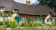 Quaint traditional rose-covered thatched cottage, Prior Bank, at Great Milton in Oxfordshire, UK