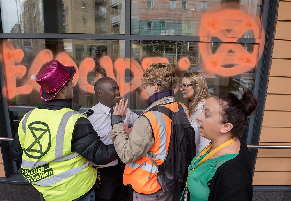 © Licensed to London News Pictures. 08/10/2018. Bristol, UK. Activists use chalk spray to write on the windows of Bristol Magistrates Court during the 'Extinction Rebellion' campaign event 'Make Ecocide Law' about the threat of climate change, at Bristol Magistrates Court and Marlborough Street. The campaign wants to make ecocide a crime in UK law, saying the threat of climate change threatens the lives of millions of people on the planet. The campaign is organised by Rising Up, and the event happened on the day that the Intergovernmental Panel on Climate Change (IPCC) has issued a special report on the impact of global warming of 1.5C. Campaigners used removable chalk spray to write on the windows of Bristol Magistrates Court, and blocked the main road before being removed by police. There were three arrests. Rising Up plans more actions in November. Photo credit: Simon Chapman/LNP