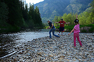 Young family playing along the Bull River at the Bull River Guard Station, one of the original ranger stations in the Kootenai National Forest. Bull River Valley, northwest Montana.