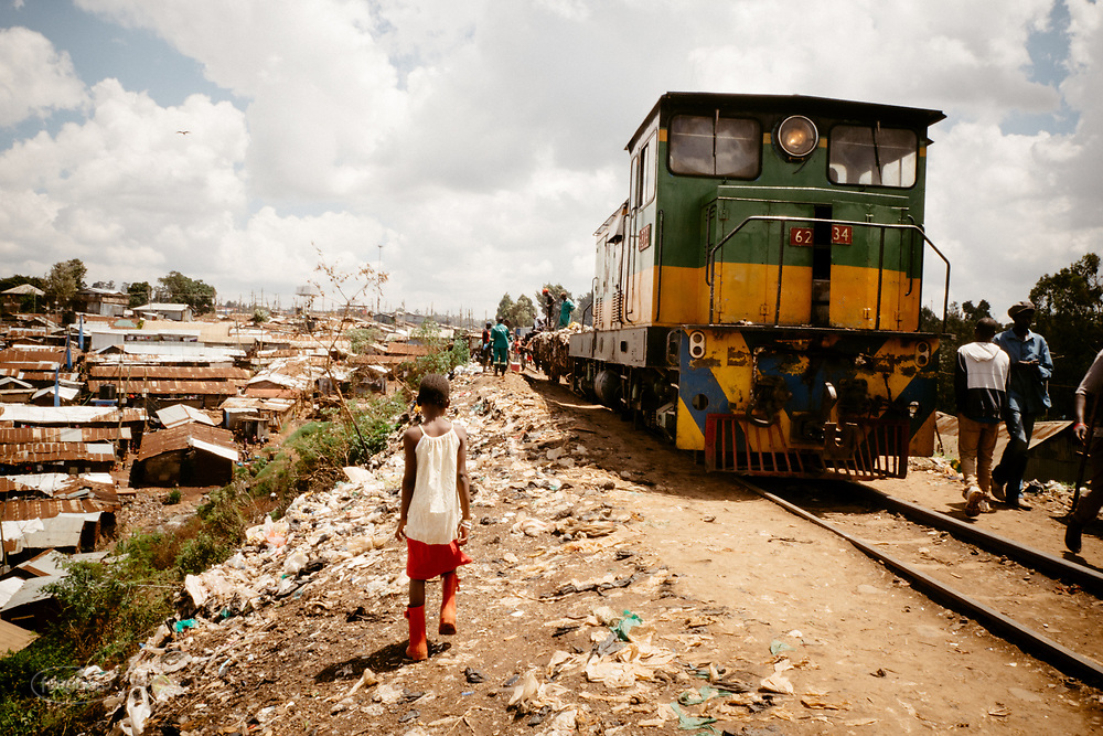 Kenia 2017: Nairobi. La ferrovia per Kibera è la strada principale sullla quale tutti si muovono, lavorano e vivono. Il treno con i rifiuti scarica qui i rifiuti appena arrivati.