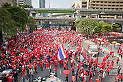 "Apr 4, 2010 - BANGKOK, THAILAND: Red Shirt protestors in Ratchaprasong intersection. Thousands of members of the United Front of Democracy Against Dictatorship (UDD), also known as the ""Red Shirts"" and their supporters moved their anti government protests into central Bangkok Apr. 4 when they occupied Ratchaprasong intersection, the site of Bangkok's fanciest shopping malls and several 5 star hotels. The Red Shirts are demanding the resignation of current Thai Prime Minister Abhisit Vejjajiva and his government. The protest is a continuation of protests the Red Shirts have been holding across Thailand. They support former Prime Minister Thaksin Shinawatra, who was deposed in a coup in 2006 and went into exile rather than go to prison after being convicted on corruption charges. Thaksin is still enormously popular in rural Thailand. This move, away from their traditional protest site in the old part of Bangkok, has gridlocked the center of the city and closed hundreds of stores and restaurants and several religious shrines. There has not been any violence, but the government had demanded that the Red Shirts return to the old part of the city.   PHOTO BY JACK KURTZ"