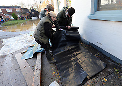 Boxing Day floods.. Residents in Yalding, Kent, with plastic sheeting as they prepare for more flooding with another storm on the way, Thursday, 26th December 2013. Picture by Stephen Lock / i-Images