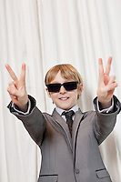 Young boy wearing sunglasses gesturing peace sign
