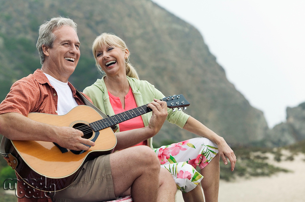 Man playing guitar with wife at beach