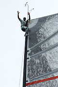 An Alinghi sailor goes to the top of the mast as measurers check SUI100 for compliance in being able to release their main from the deck. 27/6/2007