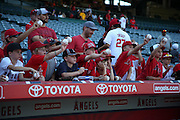 ANAHEIM, CA - AUGUST 29:  Young fans hold up baseballs in the hope of getting an autograph before the Los Angeles Angels of Anaheim game against the Oakland Athletics at Angel Stadium on Saturday, August 30, 2014 in Anaheim, California. The Angels won the game in a 2-0 shutout. (Photo by Paul Spinelli/MLB Photos via Getty Images)