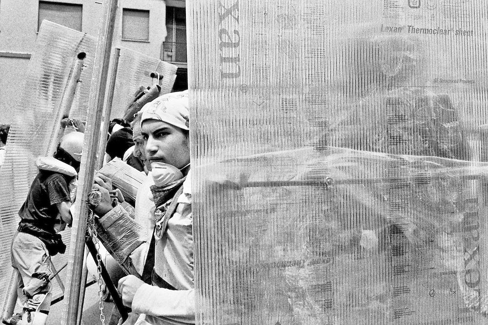 Genova, venerdì 20 luglio 2001. Giornata delle piazze tematiche. Corteo della disobbedienza civile. Manifestante dietro le barriere in plexiglas.