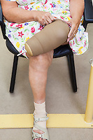 Low section of a senior woman adjusting prosthetic sleeve while sitting on chair