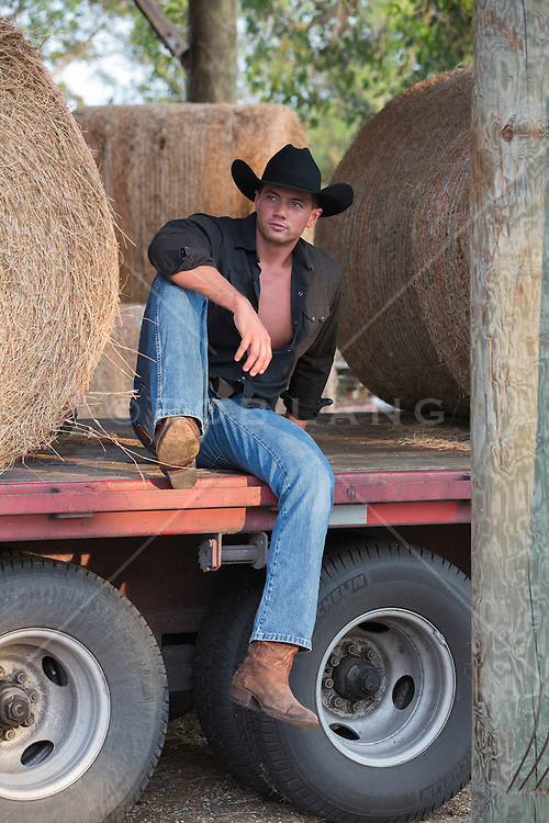 good looking cowboy seated on a flatbed truck with hay bales