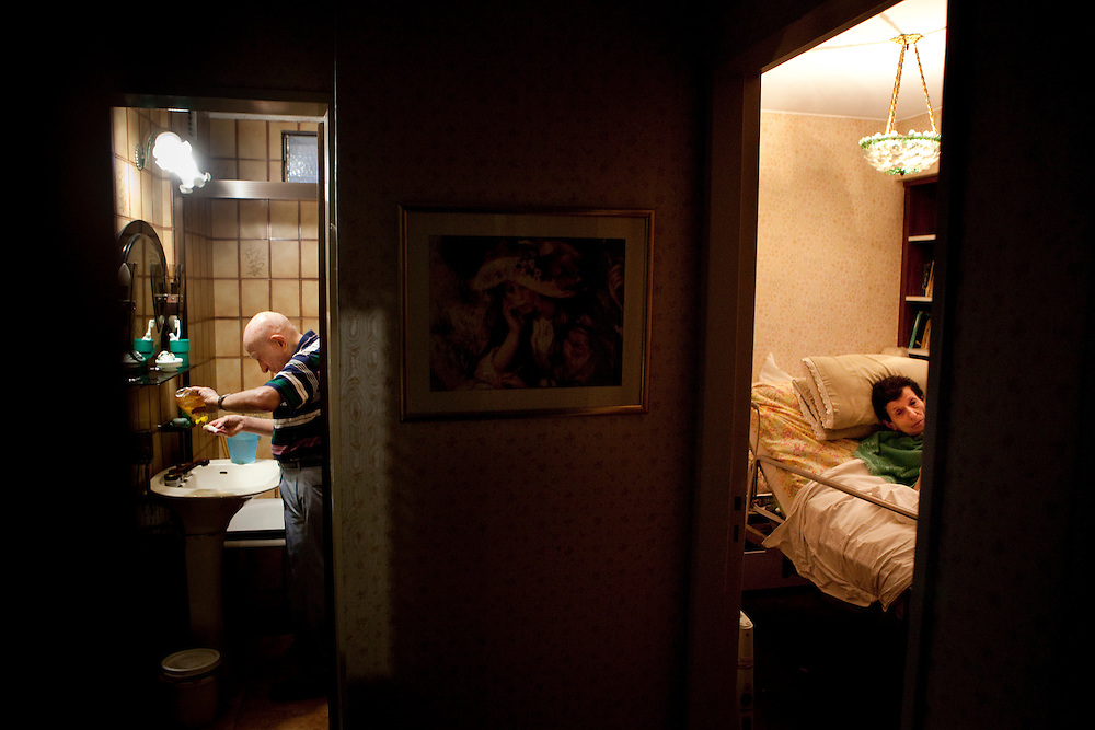 He cleans some items in the bathroom, while she lies in the orthopedic bed. According to a study by the Spanish newspaper El Mundo, caregivers of patients dedicate an average of 18 hours to the patient.