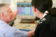 A female prison officer helps an inmate on the Vulnerable Prisoners Unit with his computer work. HMP Wandsworth, London, United Kingdom