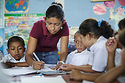A teacher helps students during class at the primary school in the town of Coyolito, Honduras on Wednesday April 24, 2013.