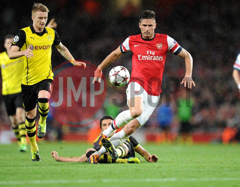 Borrusia Dortmund's Henrik Mkhitaryan tackles Arsenal's Oliver Giroud - Photo mandatory by-line: Alex James/JMP - Tel: Mobile: 07966 386802 22/10/2013 - SPORT - FOOTBALL - Emirates Stadium - London - Arsenal v Borussia Dortmund - CHAMPIONS LEAGUE - GROUP F